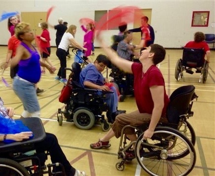 Photo of thirteen of our participants dancing with scarves, some standing, some using wheelchairs
